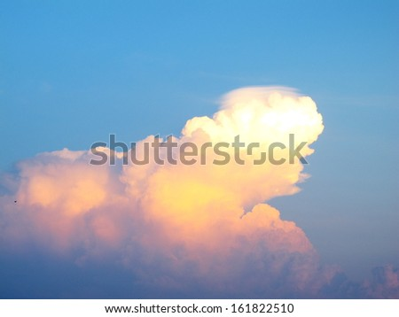 A white, orange, and pink colored fluffy cloud. - stock photo