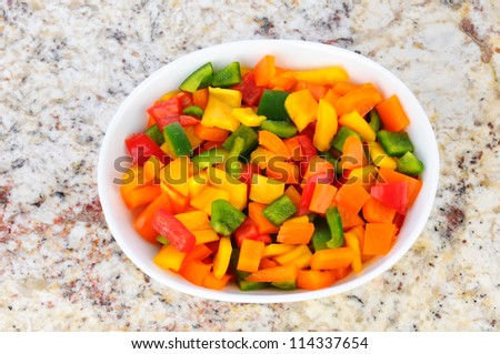 A white oval bowl full of fresh diced Green, Red, Yellow, and Orange Bell Peppers. Overhead view on a granite counter top. - stock photo