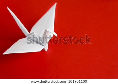 A white paper bird on a red background - stock photo