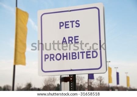 "A white ""Pets Are Prohibited"" sign with purple text."