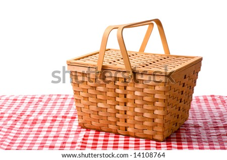 A white picnic basket on red gingham or checked tablecloth with a white background - stock photo