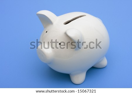 A white piggy bank on a blue background with copy space - stock photo