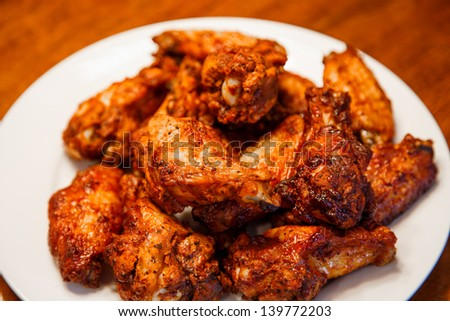 A white plate of spicy, mesquite flavored chicken wings