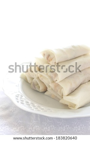 A white plate with a pile of spring rolls. - stock photo