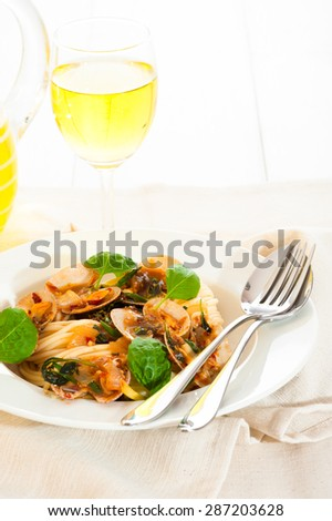A white plate with delicious spaghetti shellfish and green basil. A glass of white wine in background. - stock photo