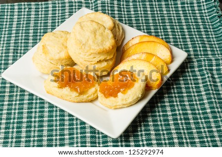 A white plate with fresh peaches and biscuits - stock photo