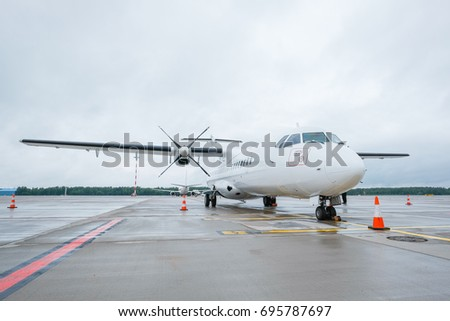 A white propeller engine plane is parked on a nearly empty airfield
