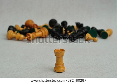 A white rook in focus with the rest of the chess pieces out of focus on a white background