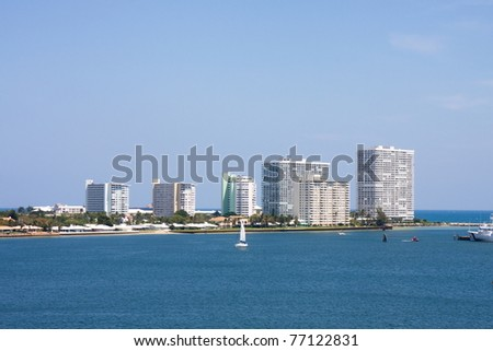 A white sailboat in a shipping channel by white beachfront condominiums