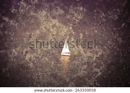 A white sailing boat  navigated by sailor in the sea. Retro aged photo with scratches and grungy texture. - stock photo