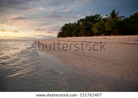A white sand beach on Gangga Island, just north of the island of Sulawesi in Indonesia, is lit by the last light of day.  This region is known for its high marine biodiversity.