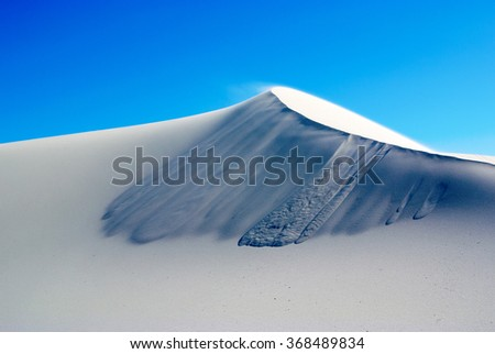 A white sand dune with wind blowing against a blue sky