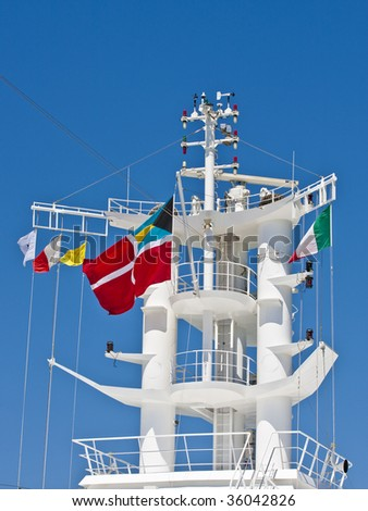 A white ships tower against a blue sky with many national flags flying in the wind