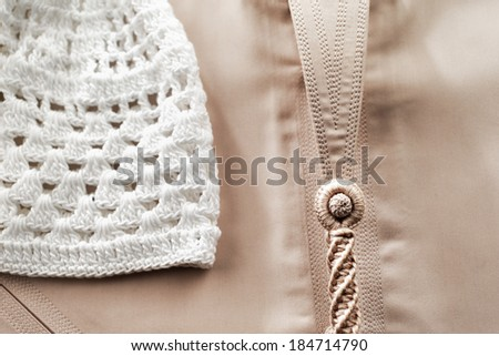 A white Skull cap is photographed here with a fawn colored Kandura, which form the basis of traditional Arab clothing for men - stock photo