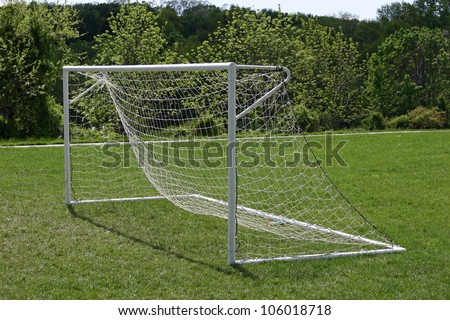 A white soccer net on a sunny soccer field - stock photo