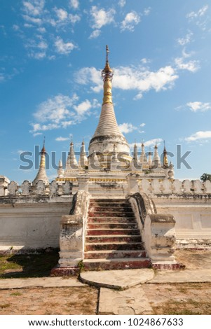 A white stupa with golden roof in the Maha Aung Mye Bon Zan monastery complex in the ancient site of Inwa or Ava near Mandalay in central Myanmar