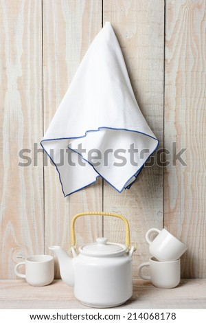 A white tea set on a rustic whitewashed setting with a towel hanging on the wall.  - stock photo