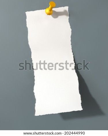 A white torn page peeling upwards attached to an isolated grey wall background by a yellow push pin - stock photo