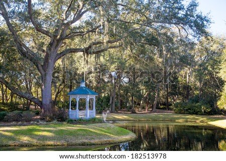 A white traditional gazebo on the shore of a lake under spanish moss draped oak trees