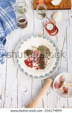 A white vintage plate with colorful aromatic ingredients  served on a white chopping board, with vintage kitchen accessories. Taken  on a white rustic background. Step on step recipe mushrooms. - stock photo