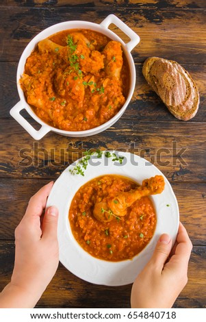 A white vintage plate with homemade chicken and lentil stew in girl's hands. Wooden rustic background, top view.