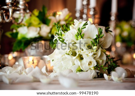 a white wedding bouquet on a dinner table during a reception. shallow depth of field - stock photo