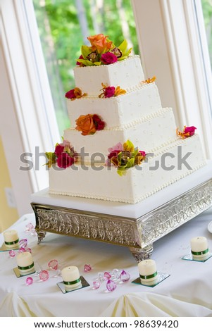 A white wedding cake with multiple layers and flowers on a silver base - stock photo