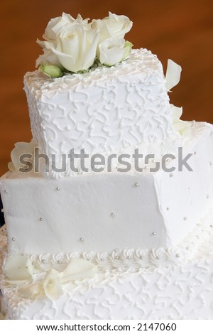 a white wedding cake with neat little swirl details and silver candy buttons, orange background - stock photo