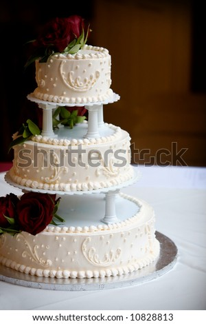 a white wedding cake with three levels and red roses