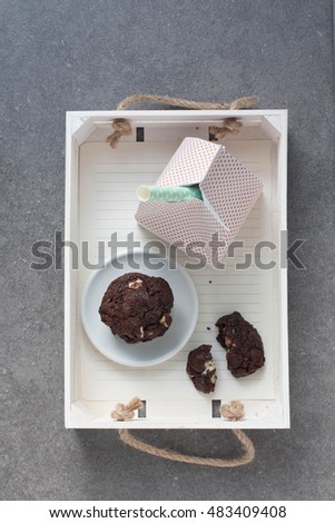 A white wooden crate with mint chip cookie and a carton of milk with a paper straw
