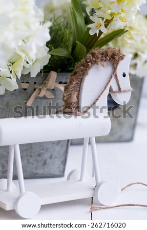 A white wooden horse with  row of three metal flower pots of yellow and white hyacinth on wood - stock photo