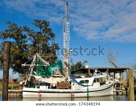 A White Wooden Shrimp Trawler Boat At Dock In A Louisiana Bayou - stock photo
