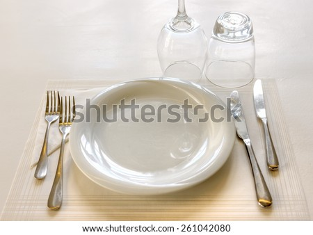 a white wooden table with a plate and 2 glasses. HDR