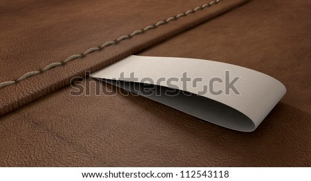 A white woven clothing label sewn into seamed brown leather - stock photo