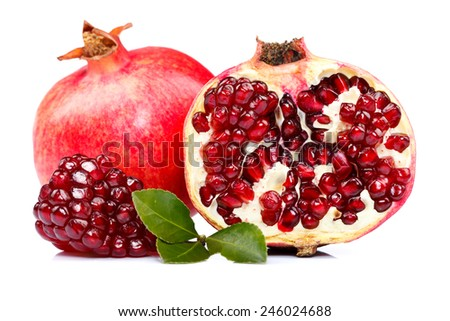 A whole and a half-cutted pomegranate with red seeds in the front - stock photo