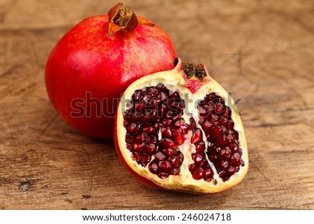 A whole and a half grenadine on a rustic wooden table - stock photo