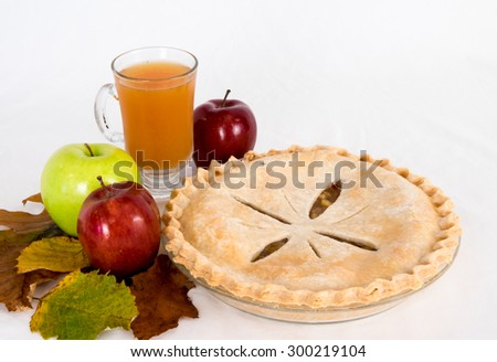 A whole apple pie with apples and cider on the side. - stock photo