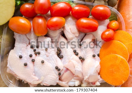 A whole chicken and soup vegetables for a chicken stock - stock photo