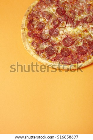 A whole, cooked and sliced peperoni pizza on a bright orange background with blank space below