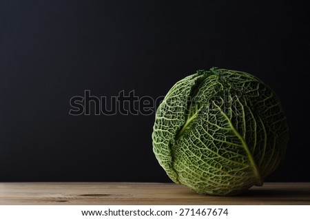 A whole head of leafy green cabbage on a wood plank table against a black chalkboard background. Moody lighting. - stock photo