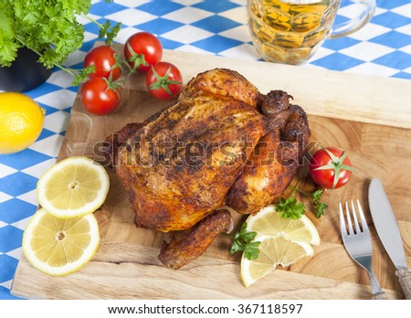 a whole roast chicken on a cutting board with side dishes
