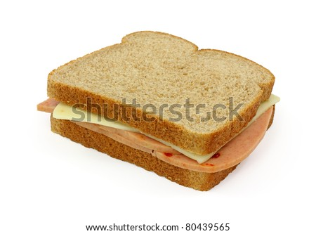 A whole wheat bread sandwich with pickle and pimento and pepper jack cheese on a white background.