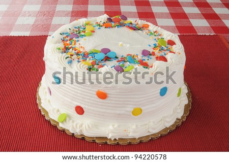 A whole white cake on a checkered tablecloth with candy sprinkles - stock photo