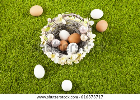 A wicker basket decorated with flowers and filled with Easter eggs on green grass