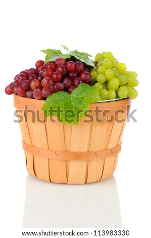 A wicker basket full of Red and Green Grapes. Vertical format on a white background with reflection.