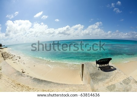 A wicker chair on a concrete outcropping overlooks a deserted beach on the Caribbean Sea on Grand Turk Island. Horizontal shot.
