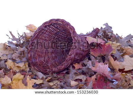 A wicker cornucopia laying on colorful fall leaves. - stock photo