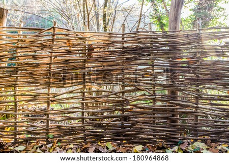 A wicker fence in summer - stock photo