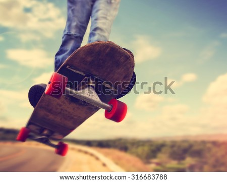 a wide angle shot of a skateboarder jumping on a road with clouds and trees in the background toned with a retro vintage instagram filter app or action effect - stock photo