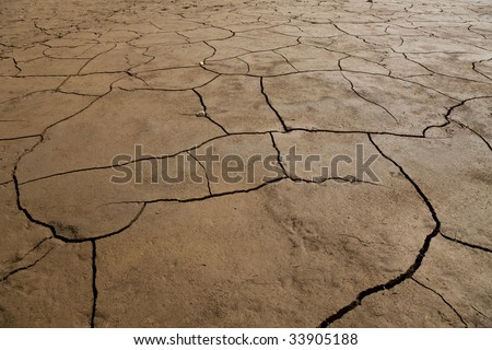 A wide angle shot of dry cracked earth. - stock photo